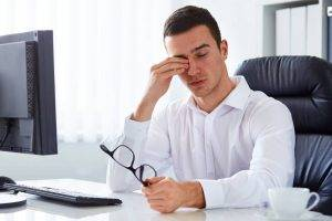man rubbing eyes due to dry eye syndrome
